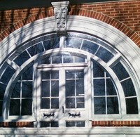 arch style storm window installation on historic building
