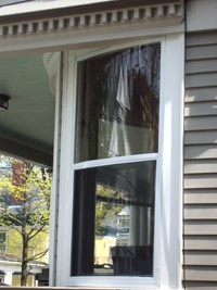 curved invisible storm window installation on historic home